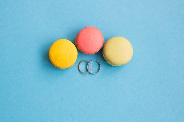 Обручальные кольца возле миндальное печенье на синем фоне. копирайс, место для текста.