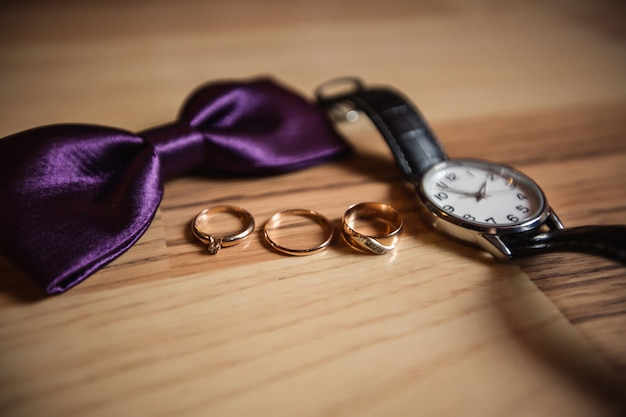 Wedding rings near purple bow tie and wrist watch for groom on wooden surface