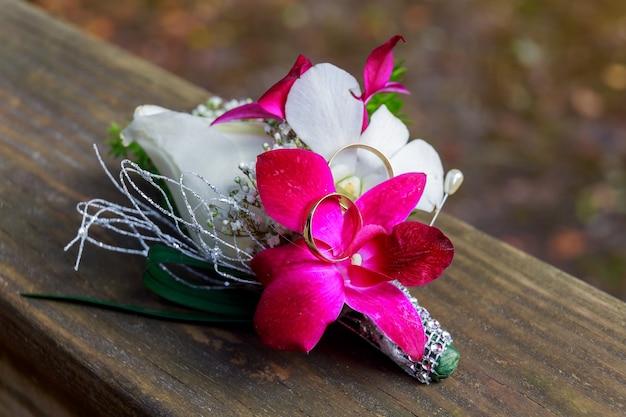 花束の近くの結婚指輪結婚指輪とアクセサリー