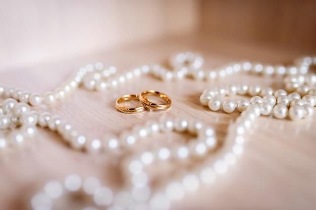 Обручальные кольца возле жемчужного кружева