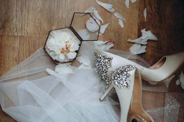 신부와 신랑의 결혼 반지는 즙이 많은 유리 상자에 있고 상자는 신부 방의 테이블에 있습니다.