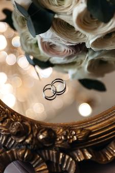 Обручальные кольца жениха и невесты на зеркальной поверхности с бокэ возле живых цветов.