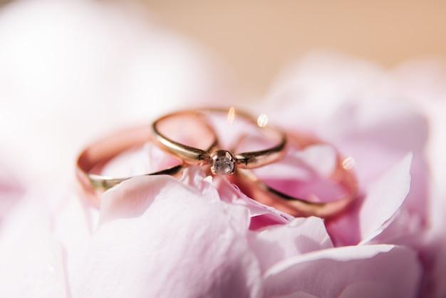 ピンクの牡丹の背景に結婚指輪