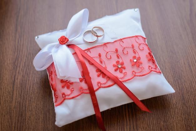 Обручальные кольца на красивой белой подушке с красным кружевом и бантами