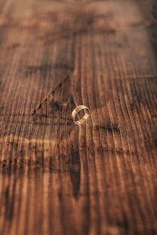 어두운 나무 배경에 결혼 반지입니다.