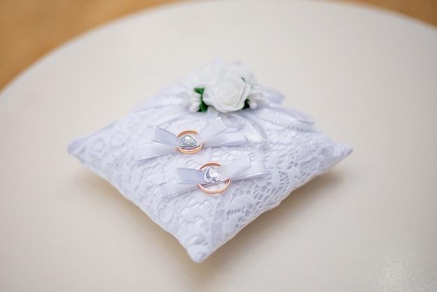 白いレースの枕の上の結婚指輪