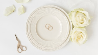 Wedding rings on ceramic plate with roses and scissor on white background