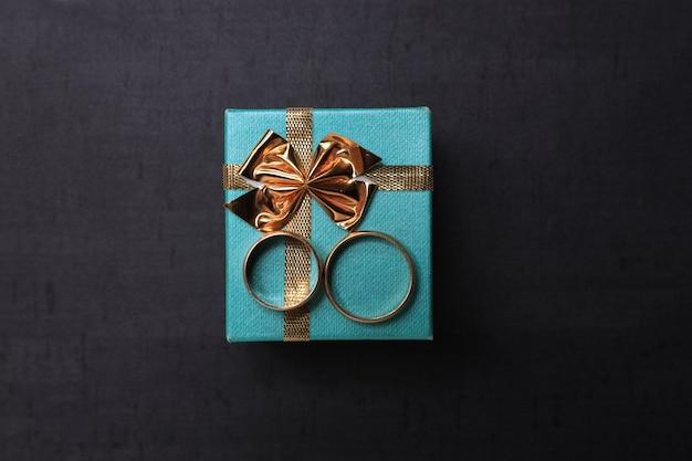 진한 회색 및 아쿠아 선물 상자에 결혼 반지. 중심 초점