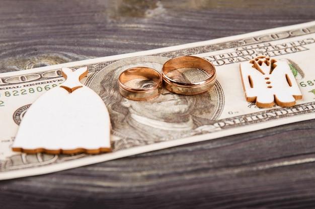 100 달러 지폐에 결혼 반지. 결혼식 비용 개념.