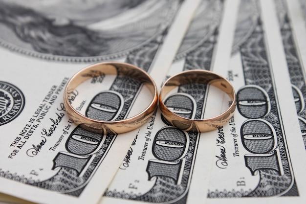 Обручальные кольца на фоне денег