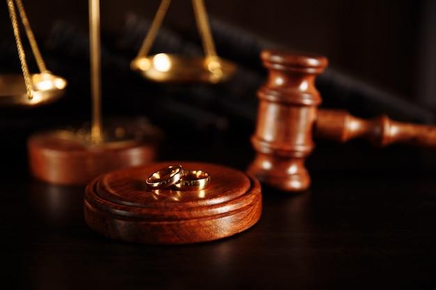 Обручальные кольца на подставке из дерева, молоток судьи на деревянном