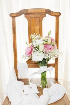 Обручальные кольца на белой подушке с шарфом и букетом на деревянном стуле возле занавеса