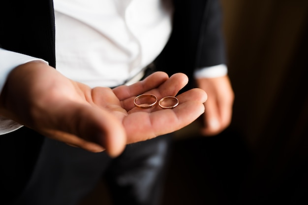 Wedding rings on the palm of the bridegroom.