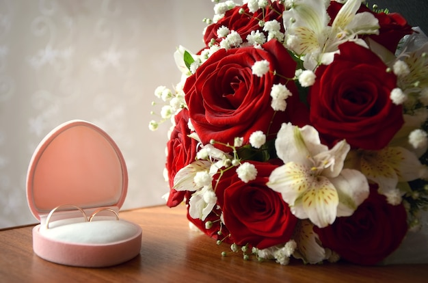 Wedding rings in a pink box next to the bride's bouquet of red roses