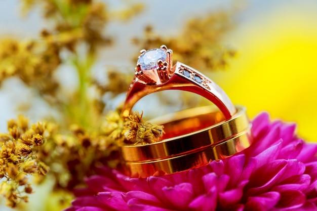 結婚指輪との結婚式のためのピンクのダリアフラワーアレンジメント