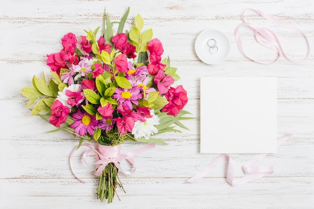 Wedding rings; ribbon and flower bouquet near white card on wooden desk