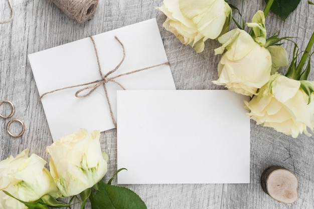 Wedding rings; roses and two white envelopes on wooden backdrop