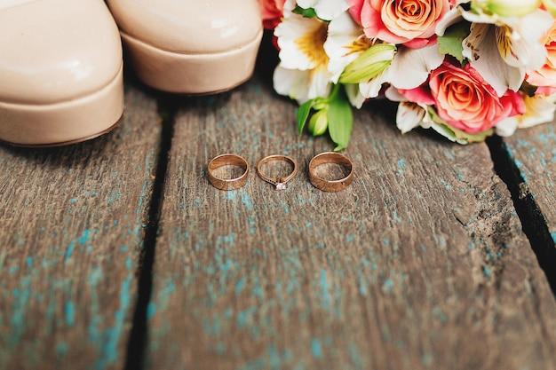 Обручальные кольца, туфли и букет на деревянных фоне. фото высокого качества