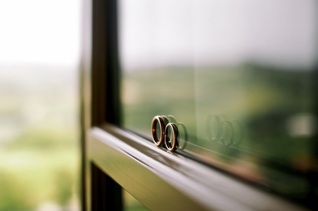 Wedding rings stand on the window