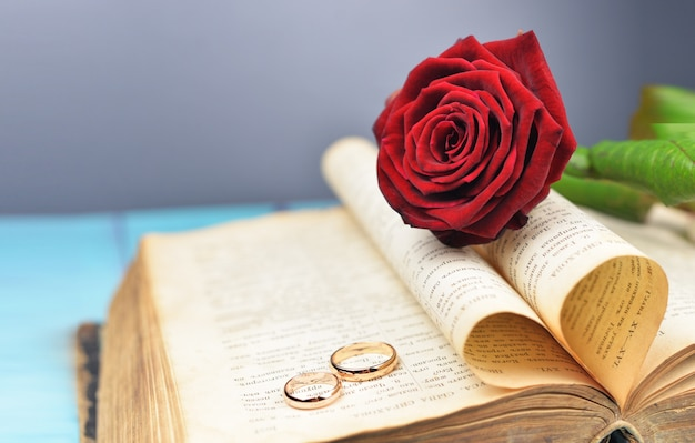 Wedding rings on a wedding with a red rose on an old book