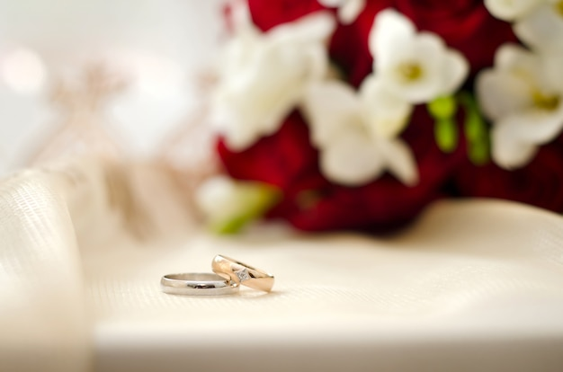 Wedding rings on a white background with a bouquet