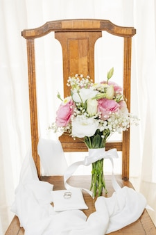 Wedding rings on white pillow with scarf and bouquet over the wooden chair near curtain