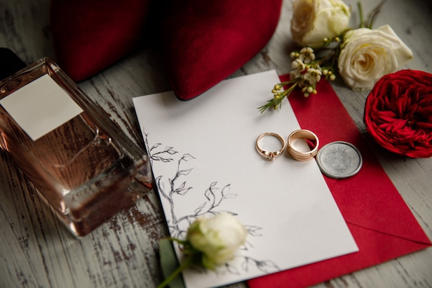Wedding rings on white and red invitation near perfume bottle