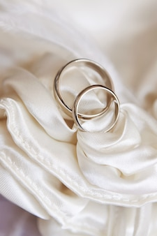 Wedding rings on white satin fabric