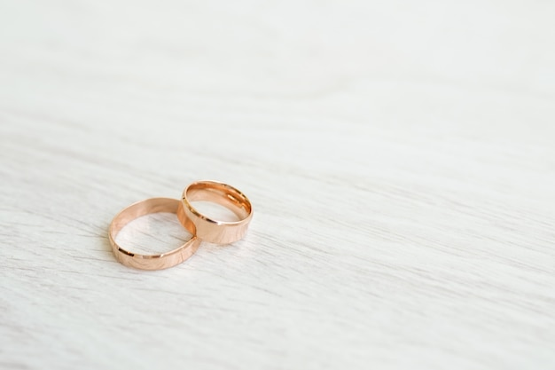 Wedding rings on white wooden surface