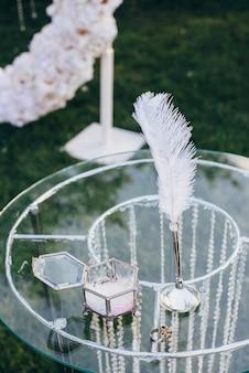 흰 꽃 아치의 유리 구슬로 장식 된 유리 테이블에 쓰기위한 펜 옆에 유리 보석 상자가있는 결혼 반지