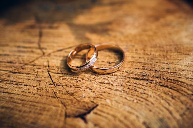 砂の背景に美しい彫刻が施された結婚指輪