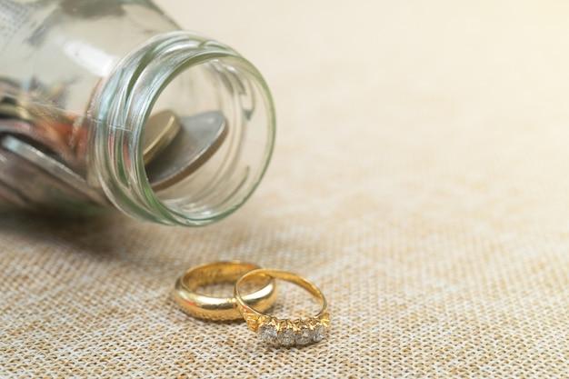 결혼을 위해 돈을 절약하는 항아리에 동전과 결혼 반지.