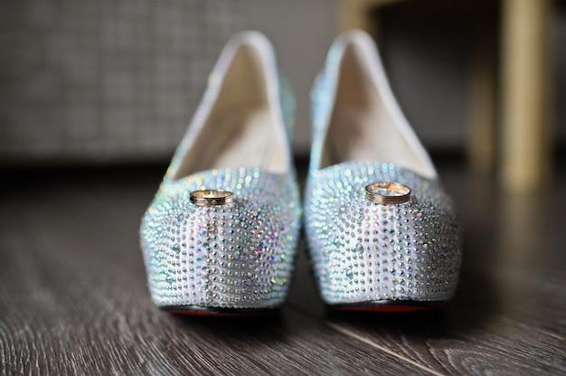 花嫁の高級靴の背景にダイヤモンドの結婚指輪をクローズアップ