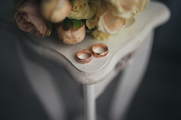 テーブルの上に花が付いている結婚指輪。高品質の写真