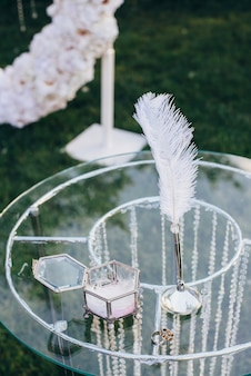 Wedding rings with a glass jewelry box next to a pen for writing on a glass table decorated with glass beads of a white flower arch