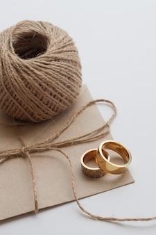招待状と茶色の糸の結婚指輪