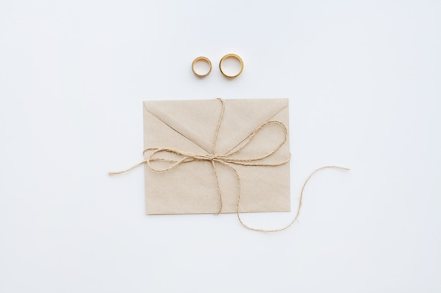 Wedding rings with invitation and brown thread