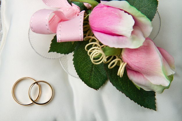 Wedding rings with roses on bridal pillow