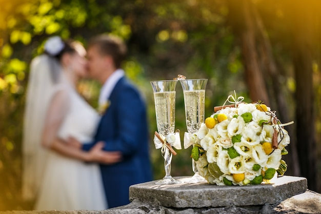 Wedding rings with roses and glasses of champagne and a kiss of the groom and bride