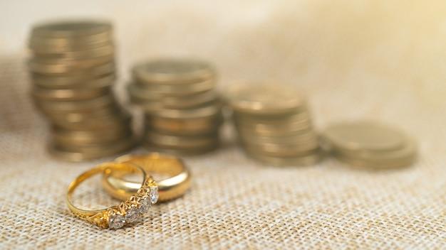 結婚のためのお金を節約するコインのスタックと結婚指輪
