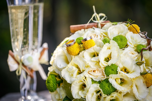 Wedding rings with wedding bouquet from beige roses, cinnamon, a lemon, a lime and glasses of champagne