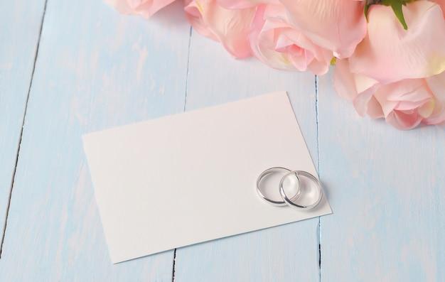 青い木製のテーブルに白いカードの紙と結婚指輪