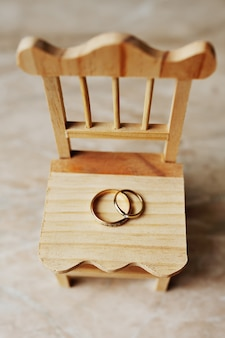 Wedding rings on a wooden chair