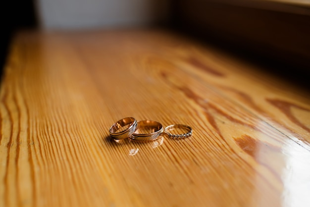 Wedding rings on a wooden surface.