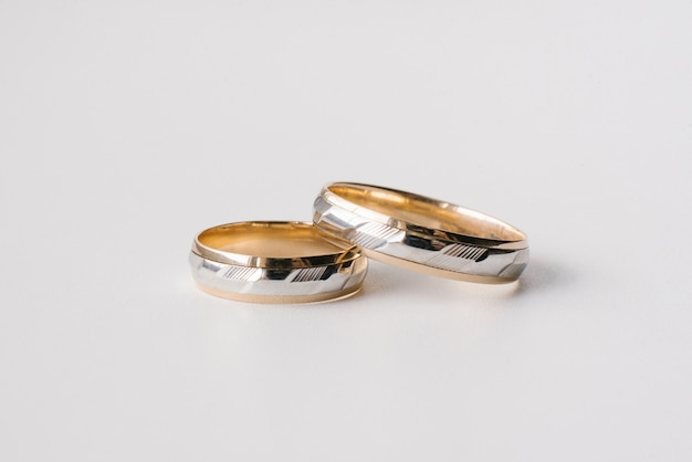 Wedding rings in yellow and white gold with carvings on a white background