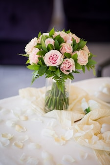 Wedding romantic bouquet from pink roses with green on the table. marriage ceremony. vertical