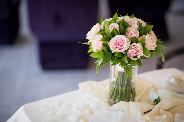 Wedding romantic bouquet from pink roses with green on the table. marriage ceremony