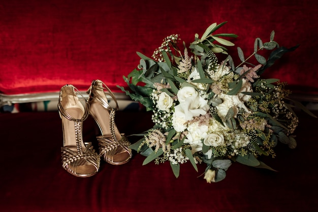 Wedding set of bridal bouquet and golden sandals shoes on red classic sofa. bride morning preparation
