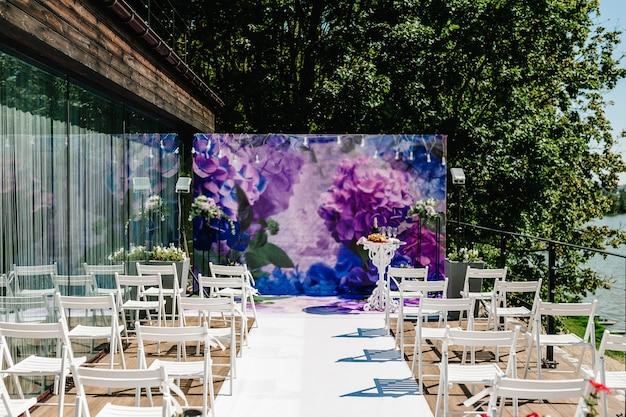 Подготовка к свадьбе. декор. деревянные стулья в банкетной зоне заднего двора. арка для свадебной церемонии декорирована цветами и зеленью.