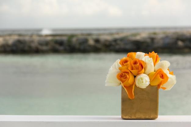 Свадебное оформление ведро с белыми и оранжевыми цветами на пляже. специальная церемония празднования у моря концепции
